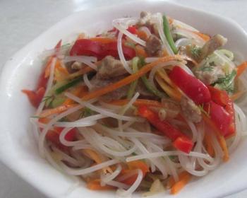 салат с фунчозой, корейской морковью, кусочками куриного филе, свежими огурцами, зеленью и красным сладким перцем в белой тарелке