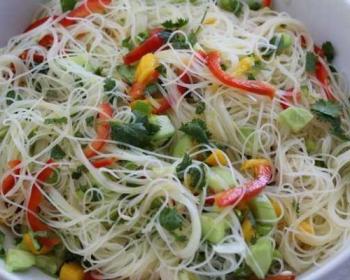 салат с фунчозой и овощами в белой глубокой тарелке