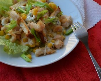 салат с яблоками, курицей, сухариками и зеленью на белой тарелке на столе с красной скатертью, рядом лежит салфетка и вилка