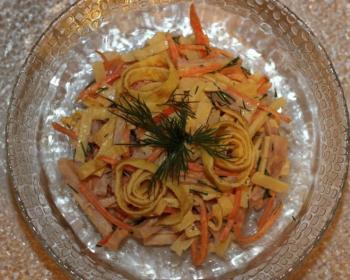 салат с яичными блинчиками и ветчиной в стеклянной прозрачной тарелке, украшенный укропом