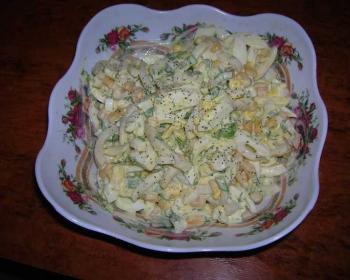 на столе стоит большая пиала с узорами, внутри лежит салат с кальмарами и кукурузой, заправленный майонезом, сверху салат, присыпанный черным перцем