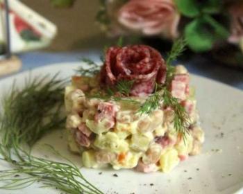 на белой круглой тарелке лежит салат с копченой колбасой и фасолью, сформированный с помощью кулинарного кольца, сверху салат украшает цветок из копченой колбасы, рядом лежит веточка укропа