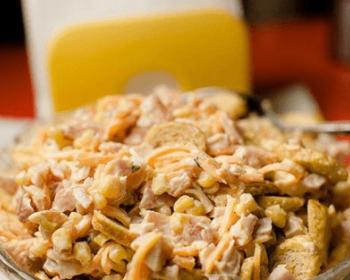 салат с корейской морковкой и копченой курицей с майонезом в тарелке с ложкой на столе