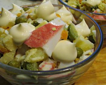 прозрачная пиала с салатом из крабовых палочек, сыра и яиц с майонезом на столе