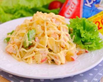 салат с креветками и консервированными ананасами, украшенный листовым салатом, в белой тарелке на столе
