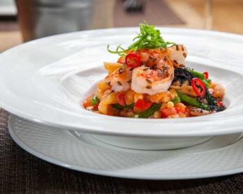на белой круглой тарелке салат с креветками и кедровыми орешками с добавление перца чили, стручковой фасоли и помидоров черри, сверху салат украшен микрогрином и семенами льна