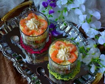слоеный салат с креветками и красной икрой в стаканах на подносе, рядом две чайные ложки, искусственные орхидеи