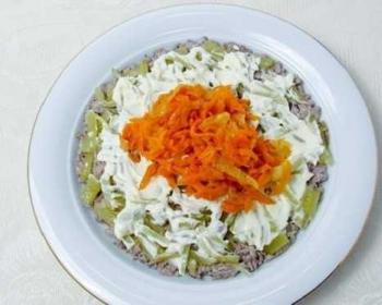 на столе стоит белая круглая тарелка, внутри лежит готовый слоеный салат с печенью, солеными огурцами и морковью