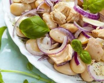 салат с тунцом, фасолью, красным луком и свежим базиликом на тарелке на столе