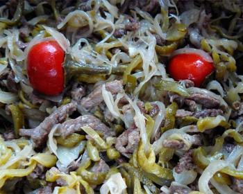 салат шахтарский из свинины, нарезанной полосочками, соленых огурцов и репчатого лука, сверху лежат два маленьких помидора