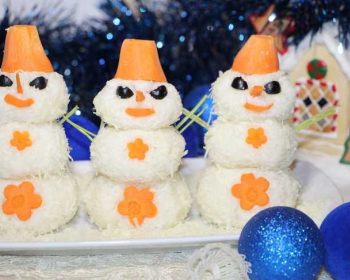салат из трески в виде снеговиков, украшенный морковью и маслинами, рядом лежат два новогодних елочных шарика