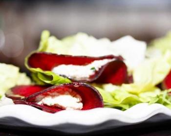 салат со свеклой, кешью и салатными листьями на тарелке на столе