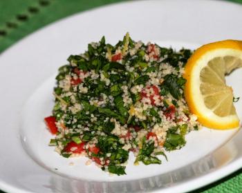 салат табуле из кускуса, помидоров, зелени и горького перца с долькой лимона на белой плоской тарелке