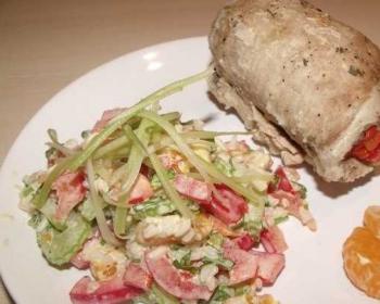 на белой тарелке лежит салат венский, рядом лежит куриный рулет