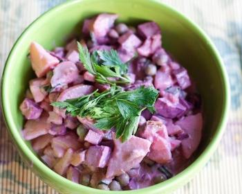 зеленая глубокая мисочка с салатом Виолетта со свеклой, украшенным свежей зеленью, на столе рядом лежит вилка