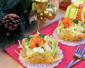 на столе лежит красная салфетка, сверху лежат две ажурные маленькие салфетки на них стоят пиалы из сыра внутри салат жемчужина с креветками, рядом две вилки и веточка елки с шишкой