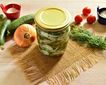 салат зимний король из нарезанных огурцов, репчатого лука и зелени в закрытой стеклянной банке на столе, рядом нечищеный репчатый лук, пучок зелени, два свежих огурца, солонка и три помидора