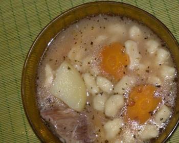 суп из салмы, моркови, картофеля и мяса в коричневой тарелке на столе, застеленном деревянным ковриком