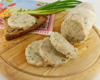 сало через мясорубку со специями в виде колбасы на деревянной разделочной доске в форме круга, рядом лежит кусочек ржаного хлеба и зеленый лук