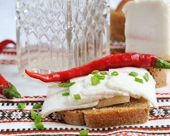 сало по-украински на кусочке хлеба, присыпанное измельченным зеленым луком, сверху стручок горького перца, на фоне графин с водкой