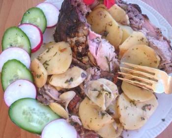 сазан фаршированный картофелем и помидорами, рядом на краю тарелки лежит огурец и редис, нарезанные дольками, сверху лежит вилка