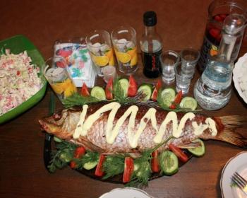 сазан, запеченный в духовке целиком, на столе в тарелке, политый соусом, рядом стоит тарелка с салатом, стаканы, стопки, графин и бутылки с тарелками