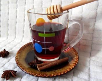 алкогольный сбитень на вине в стеклянной чашке на коричневой тарелке с палочками корицы на столе