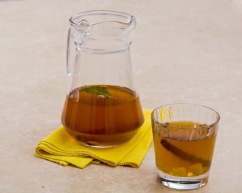 медовый сбитень с палочкой корицы, имбирем и зелеными листиками в стеклянном стакане и фужере на столе