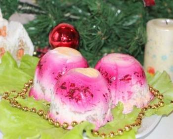 тарелочка, застеленная листьями зелени, на которых шарики из салата с сельдью под шубой с желатином, рядом елочная игрушка, бусы и свеча, на фоне искусственная елка