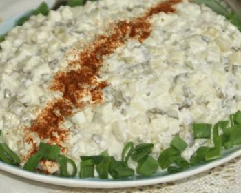 селедка под шубой с яблоками уложенная горкой на тарелку и украшенная красным молотым перцем и измельченным зеленым луком