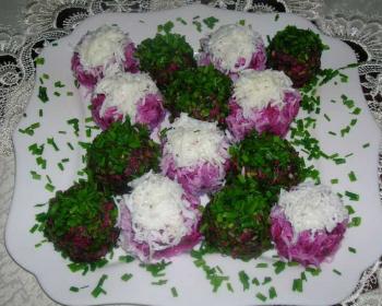 широкая белая тарелка с селедкой под шубой шариками, украшенными свежей зеленью