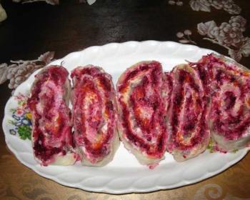 на овальном блюде лежит селедка под шубой, завернутая в лаваш и нарезанная порционными кусочками