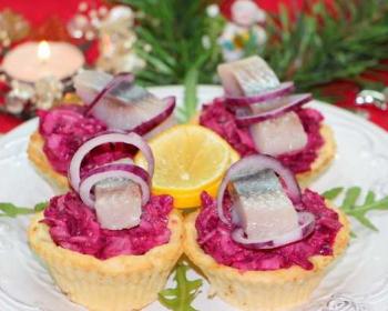 на круглой тарелке лежит четыре тарталетки, наполненные салатом селедка под шубой, сверху лежат небольшие кусочки сельди и кольца лука, в середине тарелки лежит кольцо лимона, веточки рукколы лежат на тарелке