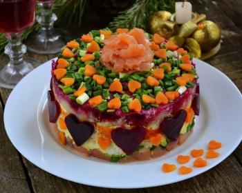 слоеный салат семга под шубой из свеклы, моркови и яиц, украшенный сердечками из свеклы, моркови и рубленым зеленым луком, на белой плоской тарелке на столе
