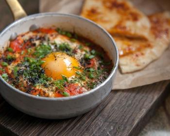 яичница с помидорами и зеленью, присыпанный специями, в сковороде на столе