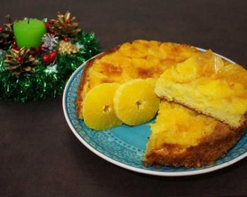 круглая шарлотка с апельсинами с отрезанным треуголным кусочком лежит в тарелке на столе, рядом свеча в новогодней мишуре