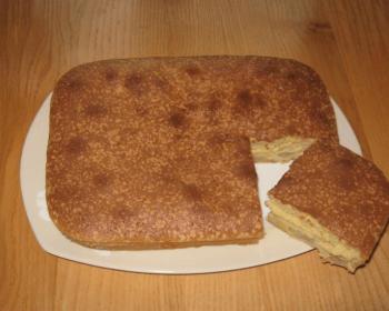 шарлотка с бананами прямоугольной формы лежит на столе на белом блюде