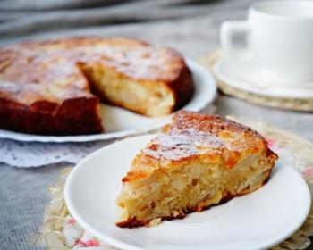 шарлотка с яблоками, приготовленная на кефире, лежит на белом круглом блюде, кусок пирога на блюдце и чашка