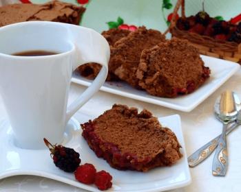 белая кружка с чаем, кусочками шарлотки, с малиной и ежевикой на блюдце на столе с ложками, плетеная корзинка с ягодами на фоне