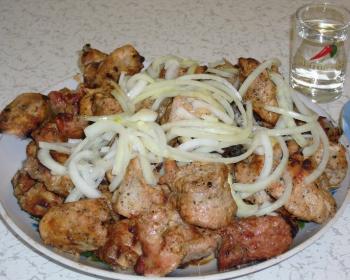 кусочки свиного шашлыка с репчатым луком на белой тарелке на столе, рядом рюмка