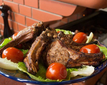 жареный шашлык из телятины, посыпанный специями, с листьями салата и целыми помидорами на плоской синей тарелке с узорами на столе