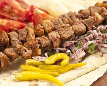 шиш-кебаб на шампурах, рядом желтый перец, помидоры, нарезанные четвертинками, полукольца репчатого лука, специи и мелко нарезанная петрушка на лаваше