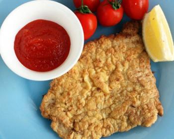 жареный свиной шницель в кляре с долькой лимона, помидорами и красным соусом в белой пиале на синей плоской тарелке
