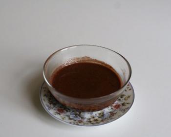 шоколадная помадка в стеклянной чаше на блюдце на столе