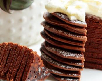 разрезанные шоколадные оладьи, сложенные стопкой, присыпанные сахарной пудрой и политые взбитыми сливками, на белой плоской тарелке