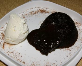 шоколадный фондан в разрезе на тарелке с шариком ванильного мороженого