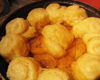 штрудель с кусочками мяса, картофелем и тестом в сковороде на столе