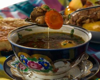 пиала с шурпой на блюдце с ложкой гущи зачерпнутой из супа