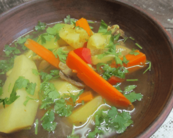 шурпа по-татарски, в состав которой входит баранина, картофель, морковка, помидор, болгарский перец, зелень в бульоне в глубокой глиняной тарелке на столе