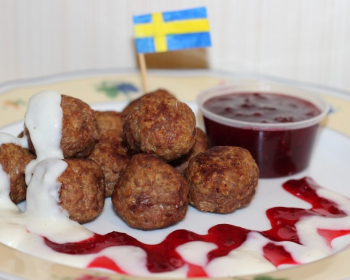 шведские фрикадельки, сложенные горкой в тарелке и политые соусом, рядом плошка с бурсничным соусом